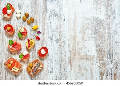 Mix of appetizers / snacks. Mediterranean tapas or antipasti on a rustic wooden table. Sandwiches with salami, jamon, mozzarella, cheese, sardines, salmon, tomato, olives and basil. Copy space.