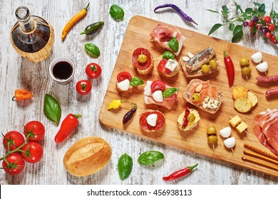 Mix of appetizers / snacks. Mediterranean tapas or antipasti on a rustic wooden table. Sandwiches with salami, jamon, sardines, salmon, mozzarella, cheese, tomato, olives, pepper, basil. Copy space.
