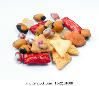 Mix of Asian snack on white background. Including Nori Maki Arare rice crackers in seaweed, glaze peanuts and fried crackers. Close up.