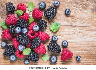Mix of berries, blueberry, raspberry, blackberry on wood background top view copy space.