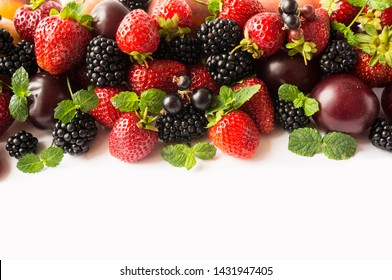 Mix berries and fruits on white background. Ripe blackberries, strawberries, blackcurrants and plums. Top view. Background berries and fruits. Various fresh summer fruits. Fresh berries close-up.