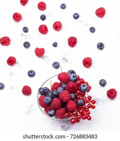 Mix of berries: red currants, raspberries, blueberries in glass bowl on white background. Top view. Selective focus.