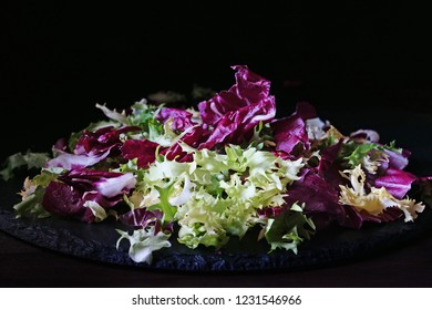 Mix of bitter-leafed vegetables, endive, radicchio, frisee and escarole leaf chicory salad over black slate platter (Cichorium endivia)
