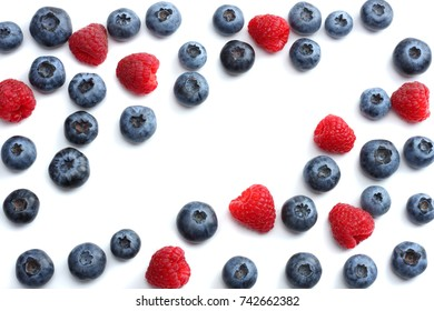 mix of blueberries, raspberries isolated on white background. top view with copy space