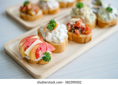 Mix canapes toast with tomato and cheese on top, selective focus
