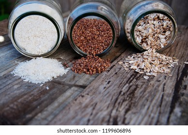 A mix of cereals - buckwheat, ots, white rice, rustic wooden table