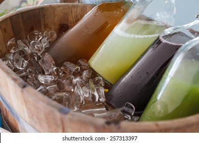 Mix cold juice bottle in wooden ice bucket