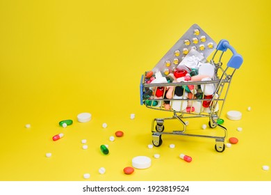 mix of colorful pills in cart on yellow background. Many tablets symbol of complex treatment, abundance of pharmacological drugs to help with pain and prevent diseases. Rich background.