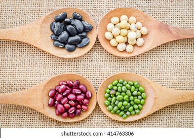 Mix from different beans, black bean, soy bean, azuki bean, mung bean in wooden spoon on the sackcloth background