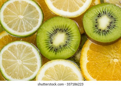 Mix of different citrus fruits involving kiwi, orange, lemon and lime