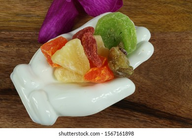mix of different dried fruits put on hand shaped ceramic plates put on woods and purple orchid beside
