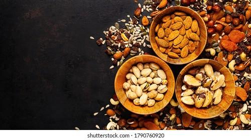 mezcla de diferentes frutos secos y nueces en tazón de madera sobre fondo rústico