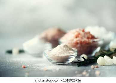 Mix of different salt types on grey concrete background. Sea salts, black and pink Himalayan salt crystals, powder, rosemary. Salt crystal balls from Dead sea. Copy space.