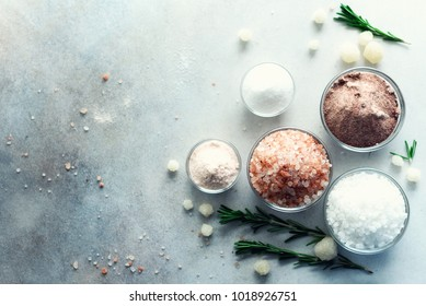 Mix of different salt types on grey concrete background. Sea salts, black and pink Himalayan salt crystals, powder, rosemary. Salt crystal balls from Dead sea. Copy space. Top view