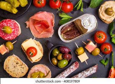 Mix of different snacks and appetizers. Spanish tapas on a black stone plate. Tapas bar. Deli, sandwiches, olives, sausage, anchovies, cheese, jamon, marinated pepper, tomatoes, canapes. Top view