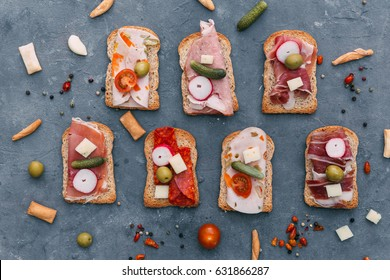 Mix of different snacks and appetizers. Spanish tapas on a black stone background. Tapas bar. Space for text. Deli, sandwiches, olives, sausage, anchovies, cheese, jamon, pepper, tomatoes. Top view