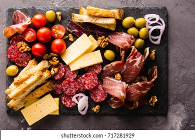 Mix of different snacks and appetizers. Spanish tapas on a black stone plate. Tapas bar. Sandwiches, olives, sausage,  cheese, jamon,, tomatoes, canapes. Top view
