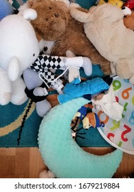 Mix of different toys laying on a floor on March 22, 2020 in Poznan, Poland. Mess contains plush animals laying on a blue carpet and wooden surface. Vertical aerial perspective.