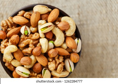 Mix of Dish of walnut, hazelnuts, almond, ketob and pistachios spilled from a cup on the background of cloth from burlap. Nuts as structure and background, macro.