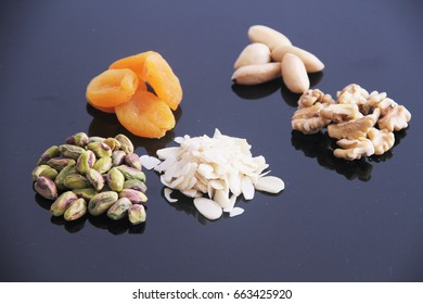 Mix of dried fruit and grain, apricot, pistachio, almond, walnut, chestnut isolated on black background