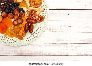 Mix of dried fruit and nuts on a beautiful vintage plate on white wooden background with copy space. View from above. Symbols of the Jewish holiday of Tu B'Shvat