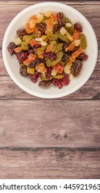 Mix dried fruit pieces in white bowl over wooden background