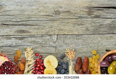 Mix of dried fruits, barley, wheat, olives, pomegranate on wooden table - symbols of judaic holiday Tu Bishvat. Copyspace background.Top view.