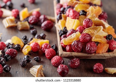 Mix of dried fruits and berries on a wooden table.