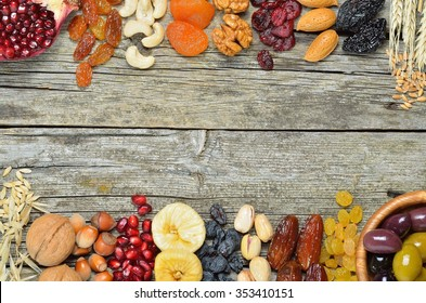 Mix of dried fruits and nuts, barley, wheat, olives, pomegranate on wooden table  - symbols of judaic holiday Tu Bishvat. Copyspace background.Top view.