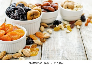 mix of dried fruits and nuts on a white wood background. tinting. selective focus