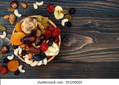 Mix of dried fruits and nuts on a dark wood background with copy space. Top view. Symbols of judaic holiday Tu Bishvat