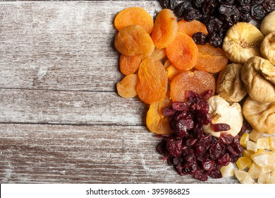 Mix of dried fruits and nuts on wooden background. Top view. Almonds, cashew and other healthy fruits. Organic and healthy