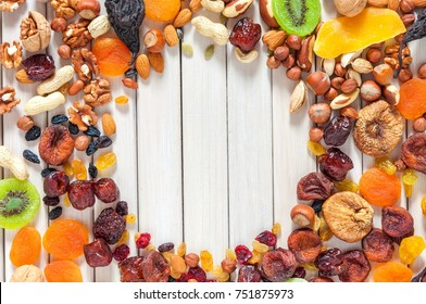 Mix of dried fruits and nuts on a white background wooden boards . Top view. Symbols of judaic holiday Tu Bishvat. Thanksgiving Day. Flat lay, top view, copy space