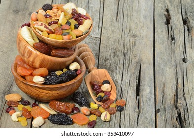 Mix of dried fruits and nuts in a wooden bowl - symbols of judaic holiday Tu Bishvat. Copyspace background.
