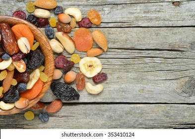 Mix of dried fruits and nuts  in a wooden bowl on wooden table - symbols of judaic holiday Tu Bishvat. Copyspace background.Top view.
