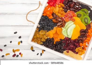 Mix of dried and sun-dried fruits, dried fruits in a wooden box on a white wooden background. View from above. Symbols of the Jewish holiday of Tu B'Shvat.