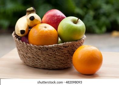 Mix of fresh apple,banana,orange, in a basket.
