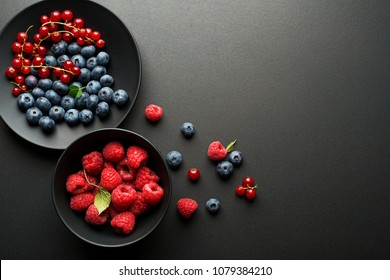 Mix of fresh berries in a bowl on black background
