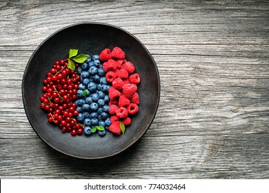Mix of fresh berries in a bowl on wooden background