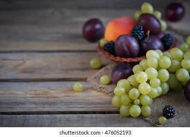 Mix of fresh berries and fruits on rustic wooden background
