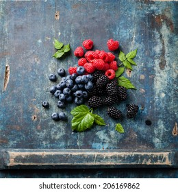 Mix of fresh berries with leaves on blue wooden background