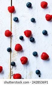 Mix of fresh berries on white wooden background. Top view.
