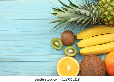 mix of fresh coconut, banana, kiwi fruit, orange and pineapple on blue wooden background. top view with copy space