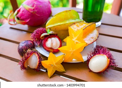Mix of fresh fruits from Thailand, dragon fruit, rambutan, carambola, mangosteen and glass of emerald tea. Sliced beautiful fresh tropical fruits.