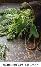 Mix of fresh Italian herbs from garden on an old table. Rosemary, temyan, oregano. Dark background