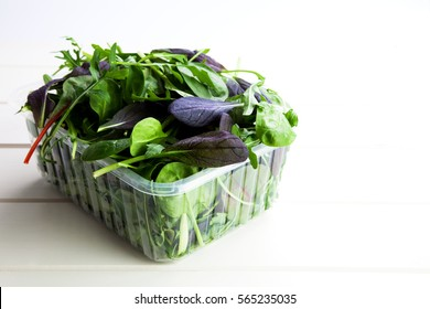Mix of fresh organic salad in plastic box packaging