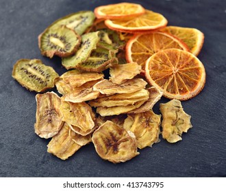 Mix of Fruit chips. Dried slices of orange, kiwi and banana on a black slate surface. Selective focus. Fruit chips