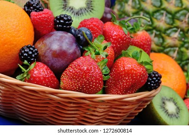 Mix of fruits on basket on wooden table