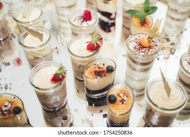 Mix of glasses with various delicious sweet desserts laying on reflective table surface. Sweets decorated with fresh fruit. Self-serving buffet table. Celebration, party, birthday or wedding concept.