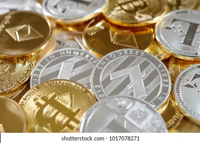 Mix of golden and silver bitcoins, litecoins and ethereum coins.